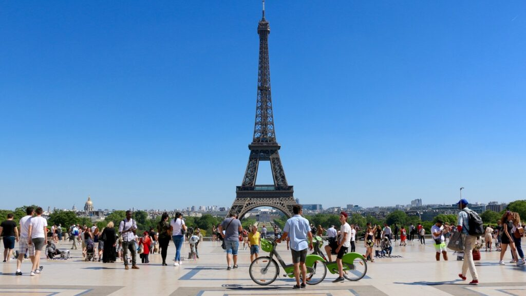 Eifel tower picture with tourists in the surrounding