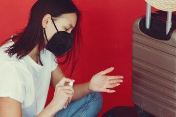 girl packing sanitizer during corona virus luggage packing