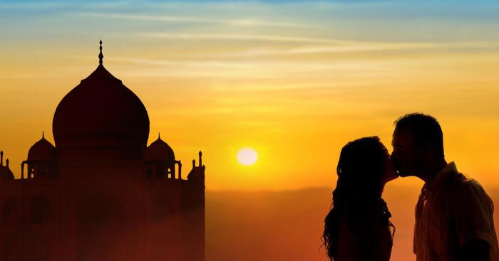 couple kissing infront of taj mahal in evening dusk