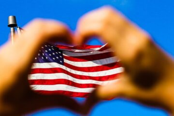 usa flag between two hands of heart shape