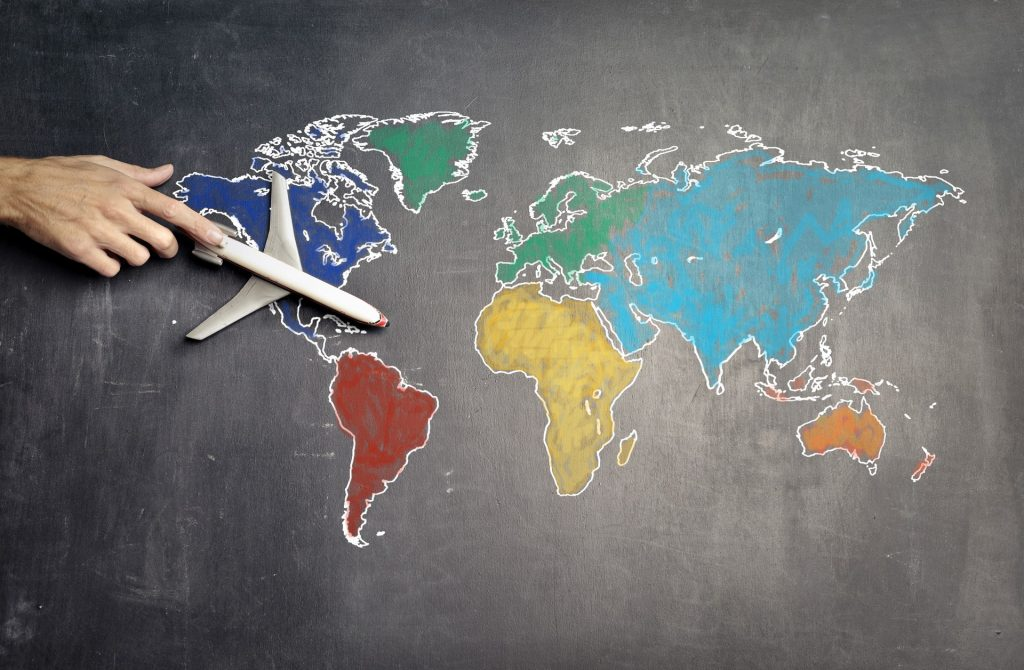 Person's finger pointing on toy airplane on chalk colored world map.