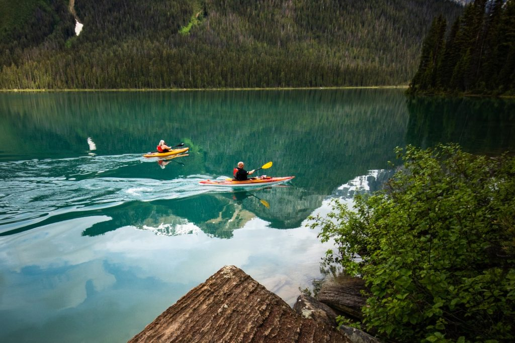 A man and woman enjoying kayaking individually on their boats while enjoying the great view of nature