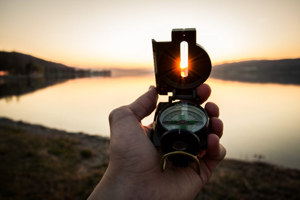 Man holding a compass infront of the lake during sunset