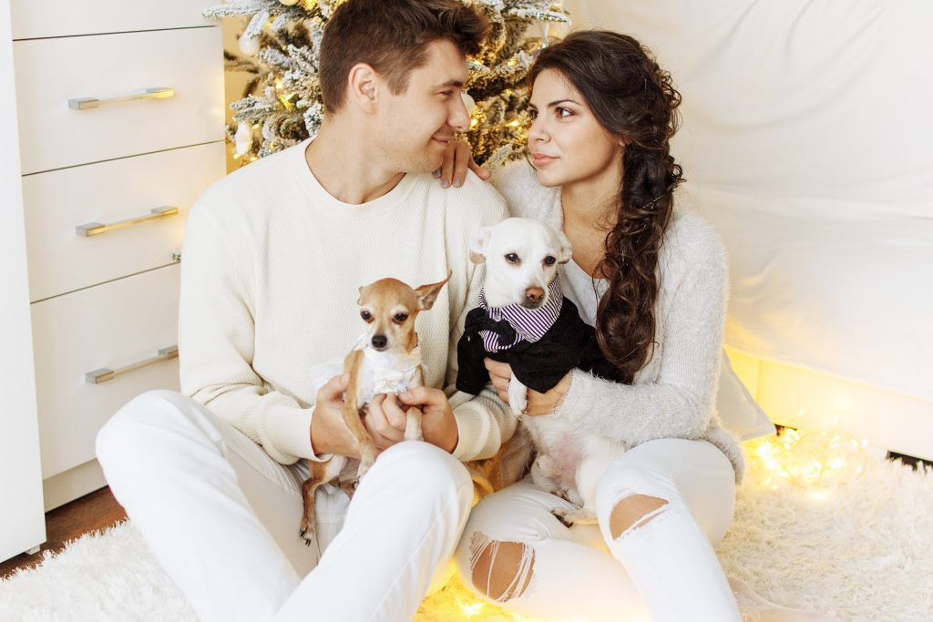 portrait of happy young couples with puppies