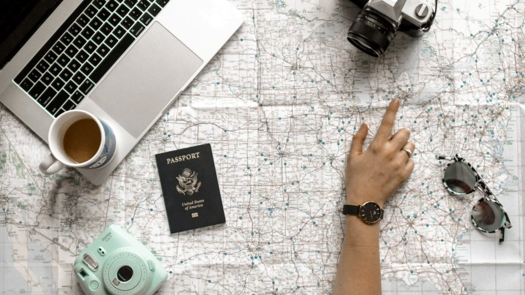 Person Pointing at Black and Gray Film Camera Near Macbook Pro and Passport
