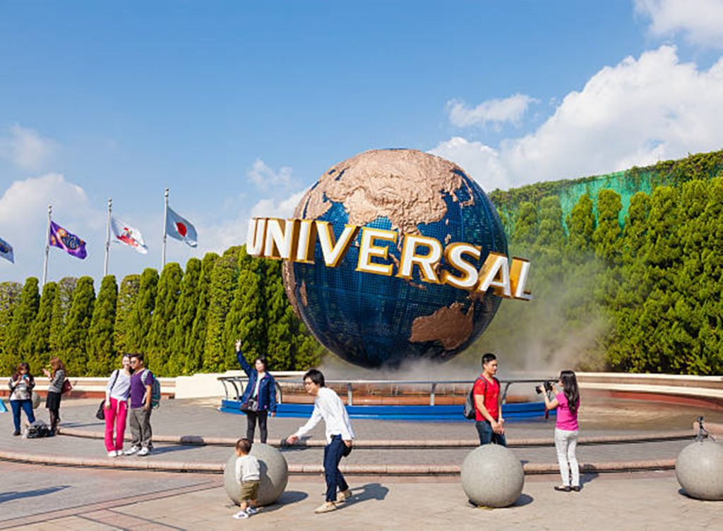 Outside Universal Studios people taking picture behind the iconic globe logo