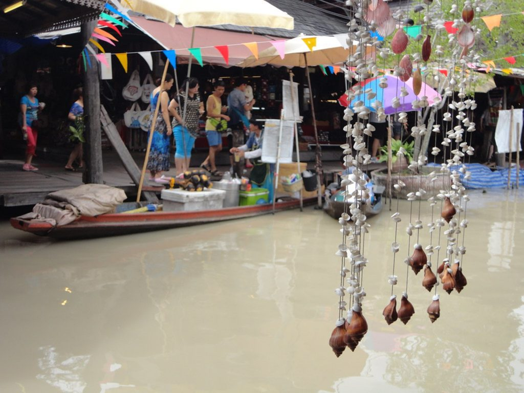 A man selling stuff on public while riding his boat on floating market