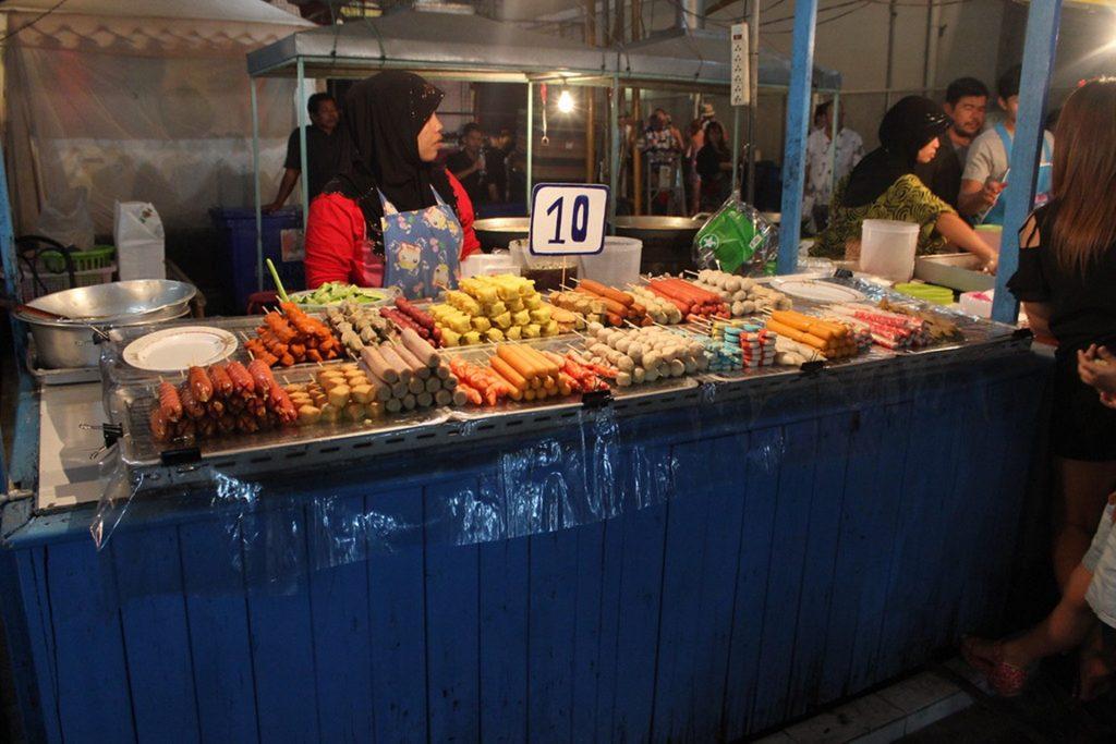 Hijabi woman selling street foods during the bazaar at night