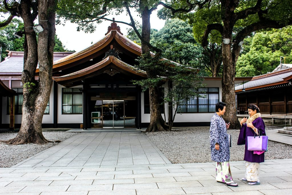 Two old women standing in front of Japanese traditional house photo