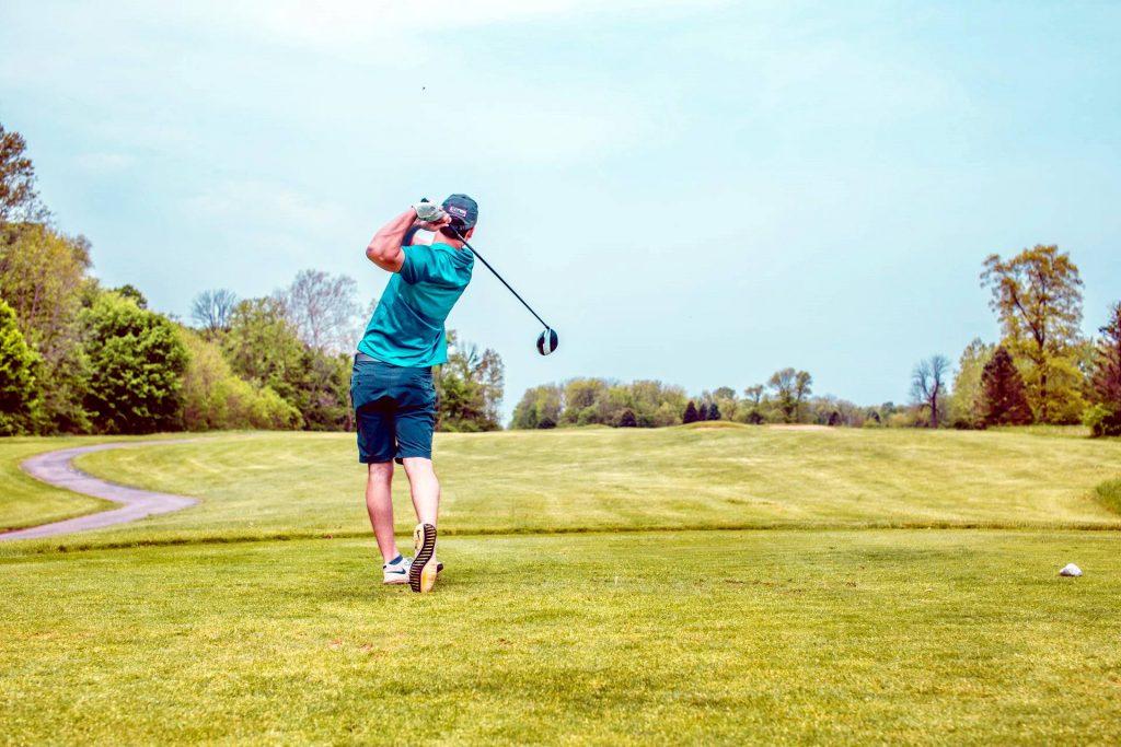 photo of man swinging golf driver photo