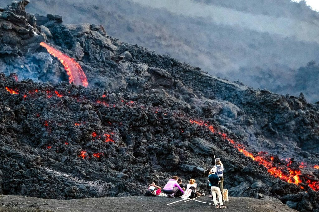 photography of people standing beside lava during daytime photo