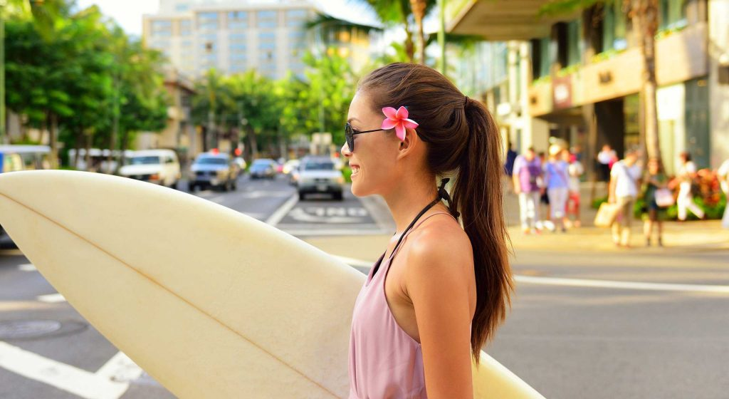 A girl carrying surfboard in the road with pink flower on her left ear.