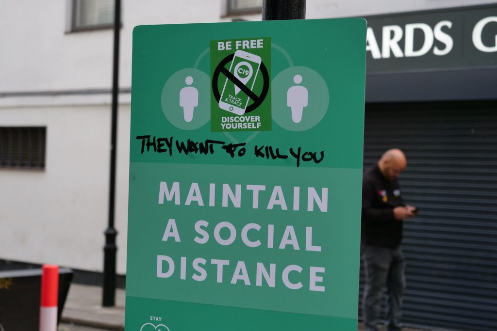 Green sign board reminder for people to maintain social distance always.