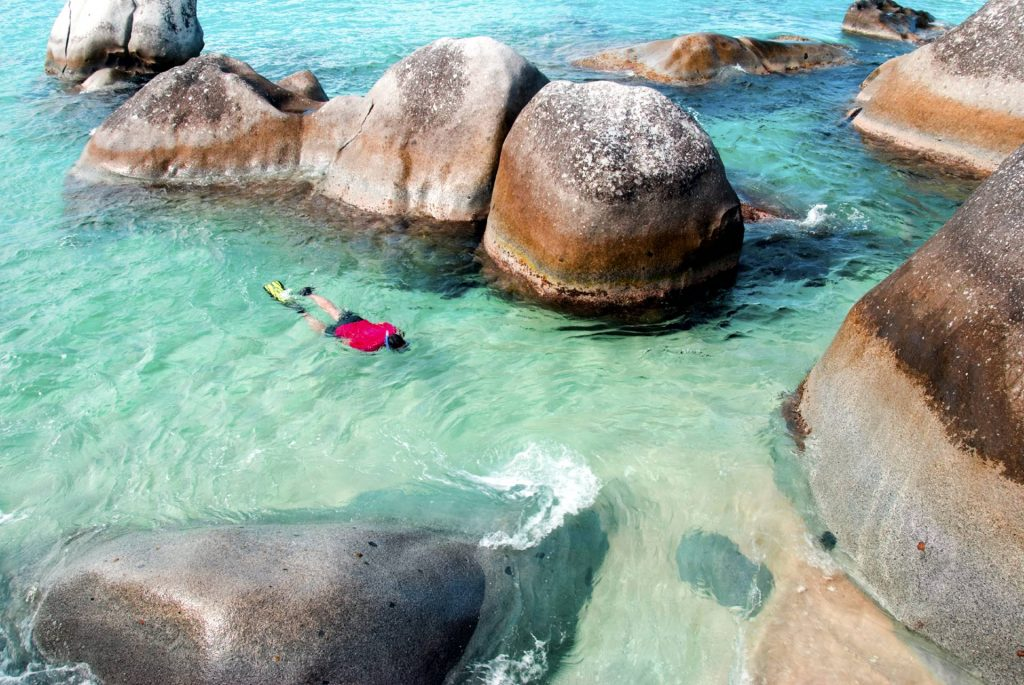 A man snorkeling near giant rock formations in the Caribbean.