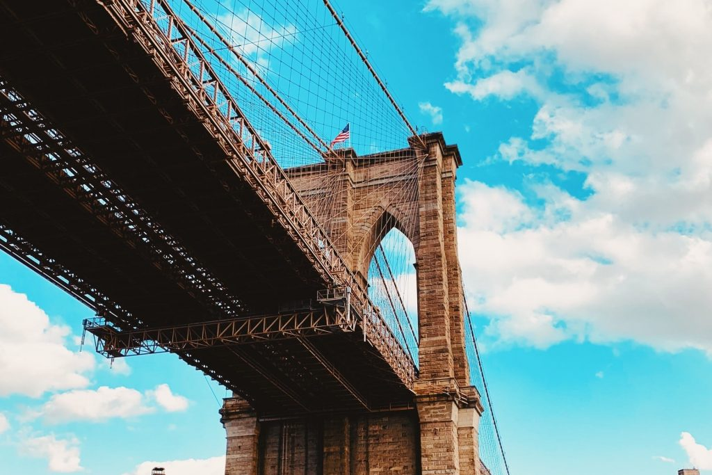 low angle photography of Brooklyn Bridge under white sky photo