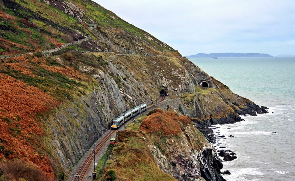 A train in the middle of cliff hanging style railroad with mountain on top and ocean on the other side.