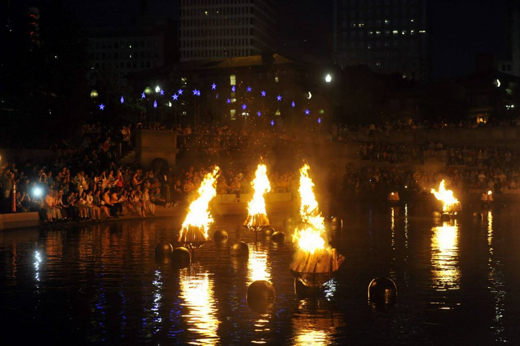 People watching floating fire show on the river