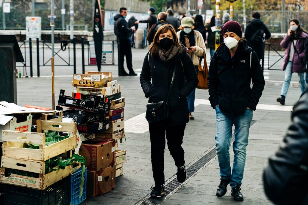 Two women walking on the road with masks