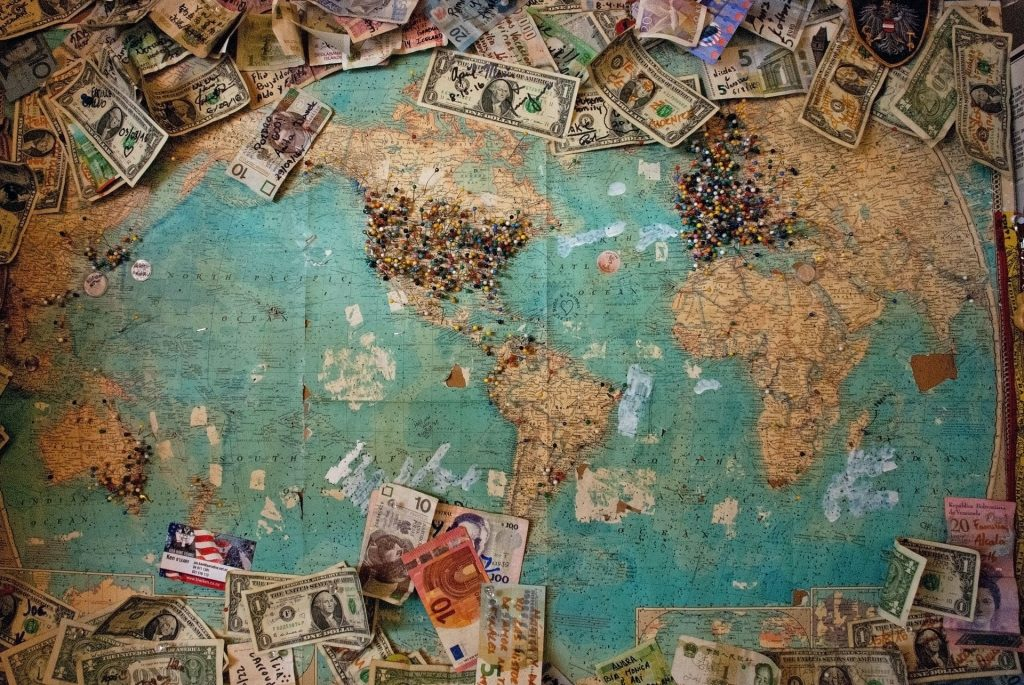 Different money currencies on top of world map with pins on it
